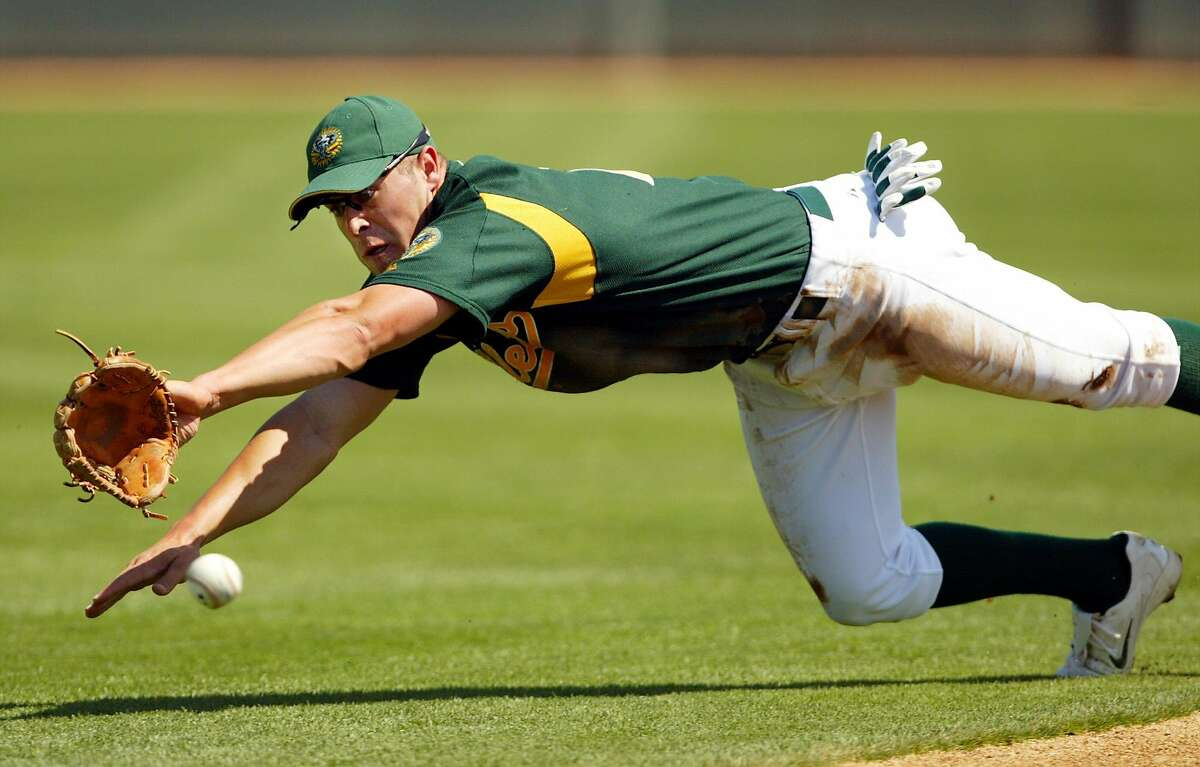 ** FILE ** Oakland Athletics new shorstop Bobby Crosby dives and misses a ground ball hit by Chicago White Sox's Paul Konerko during the first inning of their spring training game in Phoenix Wednesday, March 17, 2004. Crosby, the son of former major leaguer Ed Crosby, hit .308 with 22 home runs for Triple A Sacramento last season and did big things with his bat this spring. (AP Photo/Eric Risberg)