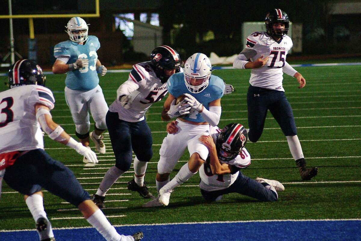 Cypress Christian's Joshua Storey (4) muscles into the end zone past Bay Area Christian's Kade Sink (56) and Bay Area Christian's Gannon Phillips (81) Friday, Dec. 4 at Friendswood High School.