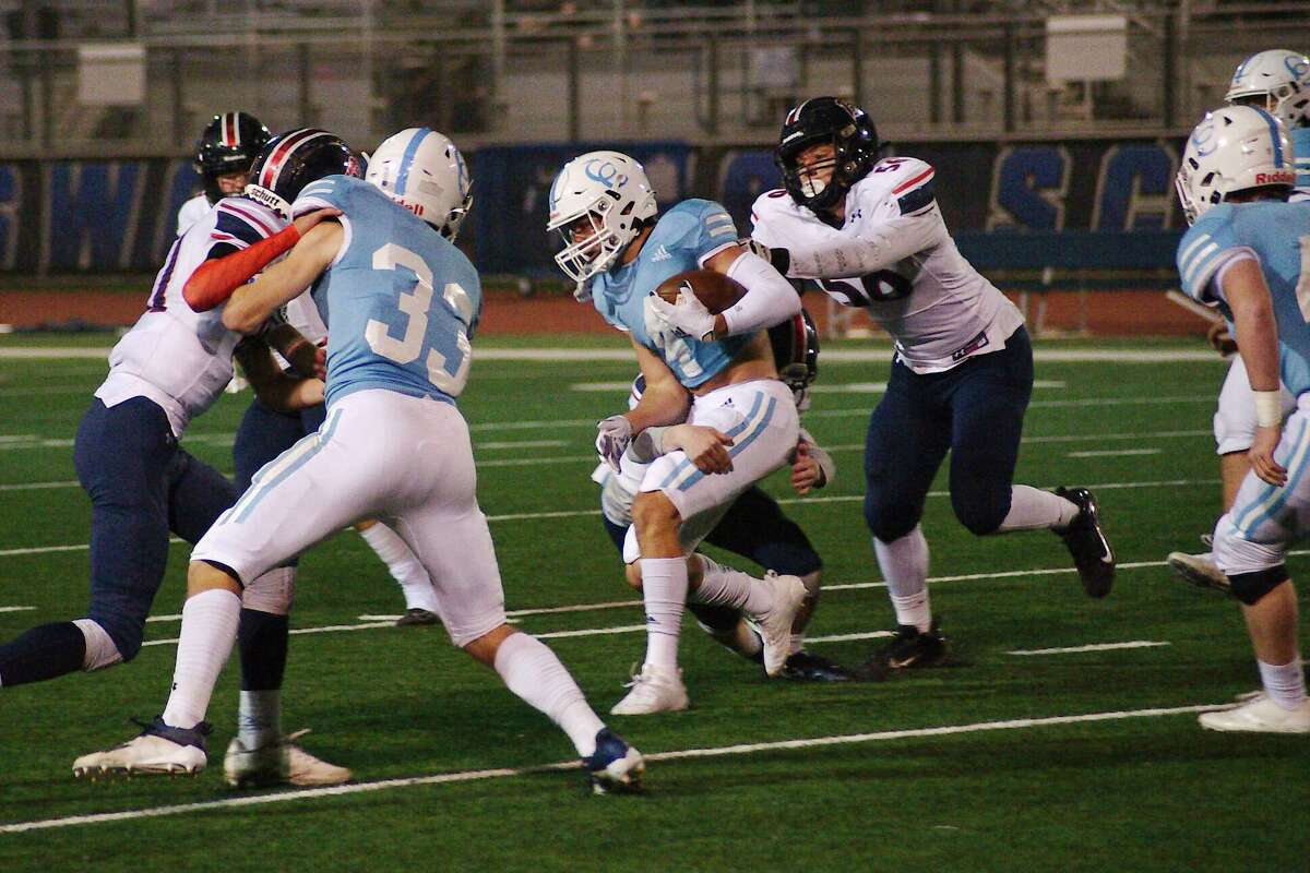 Cypress Christian's Joshua Storey (4) fights to break the tackles of Bay Area Christian's Kade Sink (56) and Bay Area Christian's Smith Nave (2) Friday, Dec. 4 at Friendswood High School.