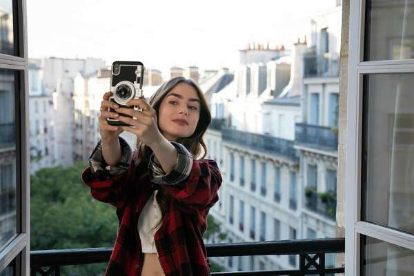 "Lily Collins as Emily in the series premiere of ""Emily in Paris,"" with her vintage camera phone case."