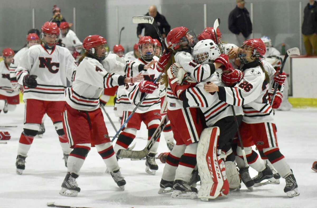 The New Canaan Rams celebrate after defeating Greenwich 3-1 to win the 2019 FCIAC girls hockey championship at the Darien Ice House.