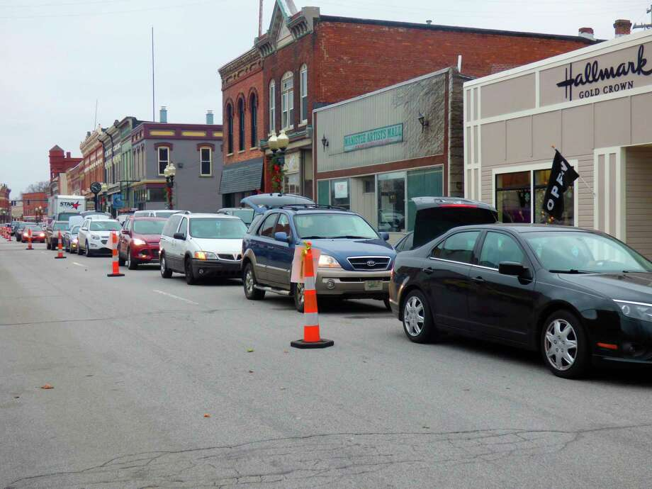 Cars line up for blocks on River Street in downtown Manistee to take part in a food pantry on Tuesday. (Scott Fraley/News Advocate)