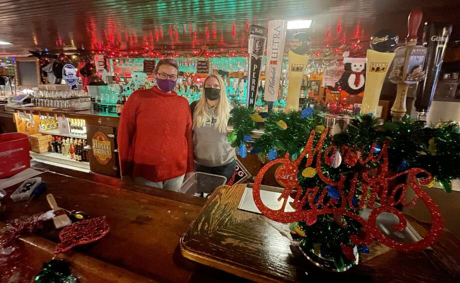 (From left) Schuberg's Bar & Grill owner Jenn Rumsey and server Maddy Ward take a break Tuesday inside the festively-decorated restaurant after a busy lunch rush. Schuberg's Bar & Grill was one of many restaurants in Mecosta County ordered to keep its dining area closed following Gov. Gretchen Whitmer's announcement Monday to extend a partial shutdown by 12 days. Ramsey said each year, the restaurant gets into the holiday spirit by decorating and this year was no different. Photo: Pioneer Photo/Bradley Massman
