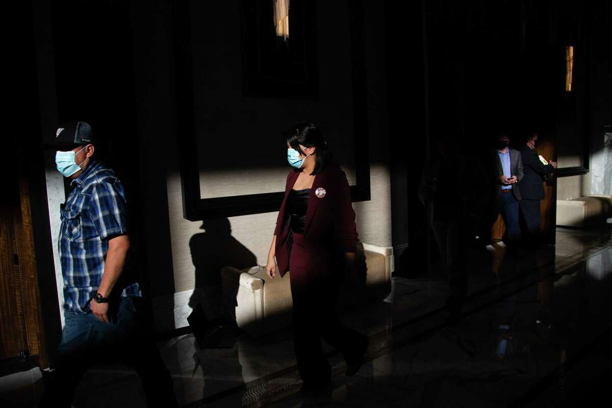 Rogelio Guillén and his daughter Lupe Guillén enter The Post Oak Hotel ballroom for a press conference, Tuesday, Dec. 8, 2020, in Houston.