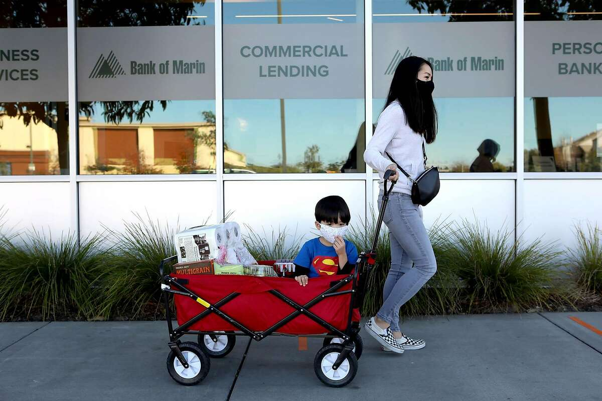 Sonny Martin pulls her son, Elliott Martin, 3, in a wagon after a shopping trip to Trader Joe's at South Shore Center while donning masks on Tuesday, December 8, 2020, in Alameda, Calif.