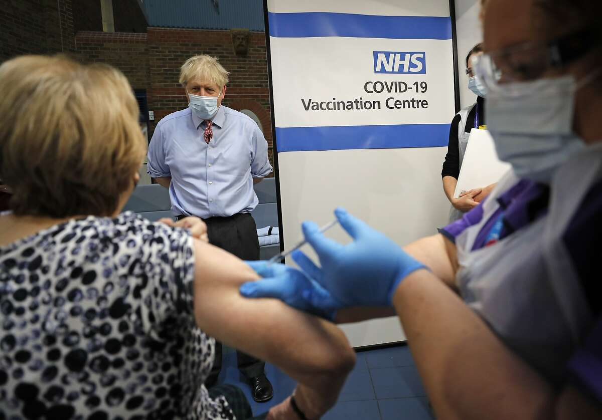 British Prime Minister Boris Johnson watches as a nurse administers a coronavirus vaccine to a woman in London.