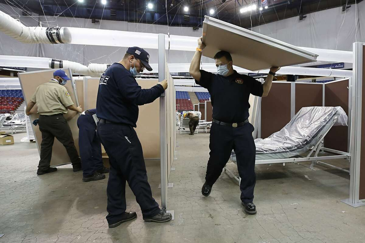 FILE - In this April 18, 2020, file photo, partitions are installed between beds as Sleep Train Arena is turned into a 400-bed emergency field hospital to help deal with the coronavirus, in Sacramento, Calif. Due to the recent spike in COVID-19 cases officials are rushing to reopen the former home of the NBA's Sacramento Kings, to patients. (AP Photo/Rich Pedroncelli, File)