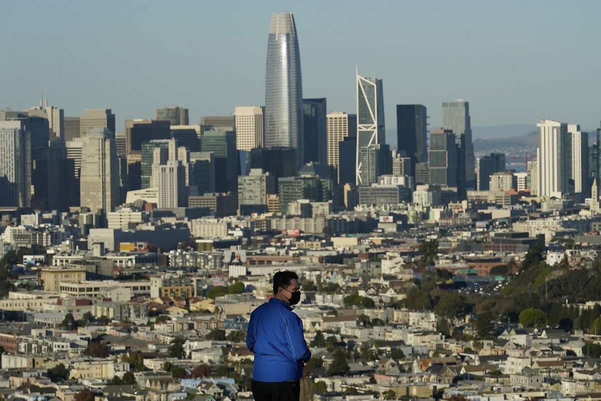 A person wearing a protective mask stands in front of the skyline on Bernal Heights Hill during the coronavirus pandemic in San Francisco, Monday, Dec. 7, 2020. (AP Photo/Jeff Chiu)
