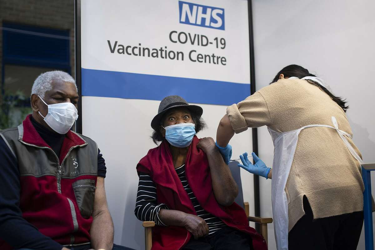 Lorna Lucas, 81, reacts as she receives the first of two Pfizer/BioNTech COVID-19 vaccine jabs shortly before her husband, Winston (L) also has one administered at Guy's Hospital, in central London on December 8, 2020. - Britain on December 8 hailed a turning point in the fight against the coronavirus pandemic, as it begins the biggest vaccination programme in the country's history with a new Covid-19 jab. (Photo by Victoria Jones / POOL / AFP) (Photo by VICTORIA JONES/POOL/AFP via Getty Images)