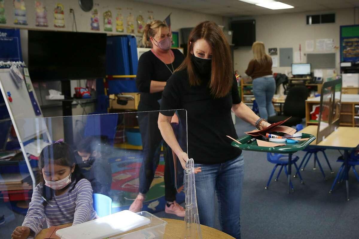 Teacher Liz Duffield (center) hands out art materials in her preschool-kindergarten combination classroom at Lu Sutton Elementary School in Novato.