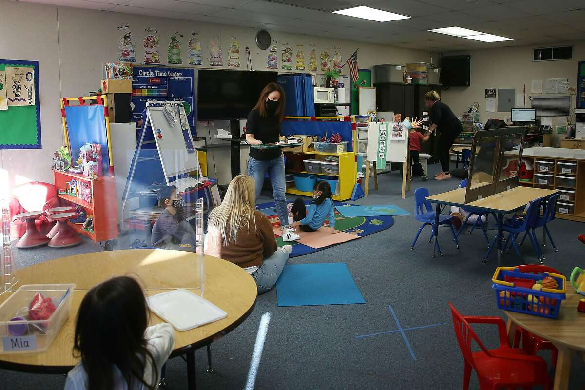 Liz Duffield (center standing), special education teacher, teaches her preschool kindergarten combination classroom at Lu Sutton Elementary School on Monday, December 7, 2020 in Novato, Calif. The COVID-19 pandemic has led to a record one-year enrollment drop of 155,000 students, according to state projections, out of 6 million.