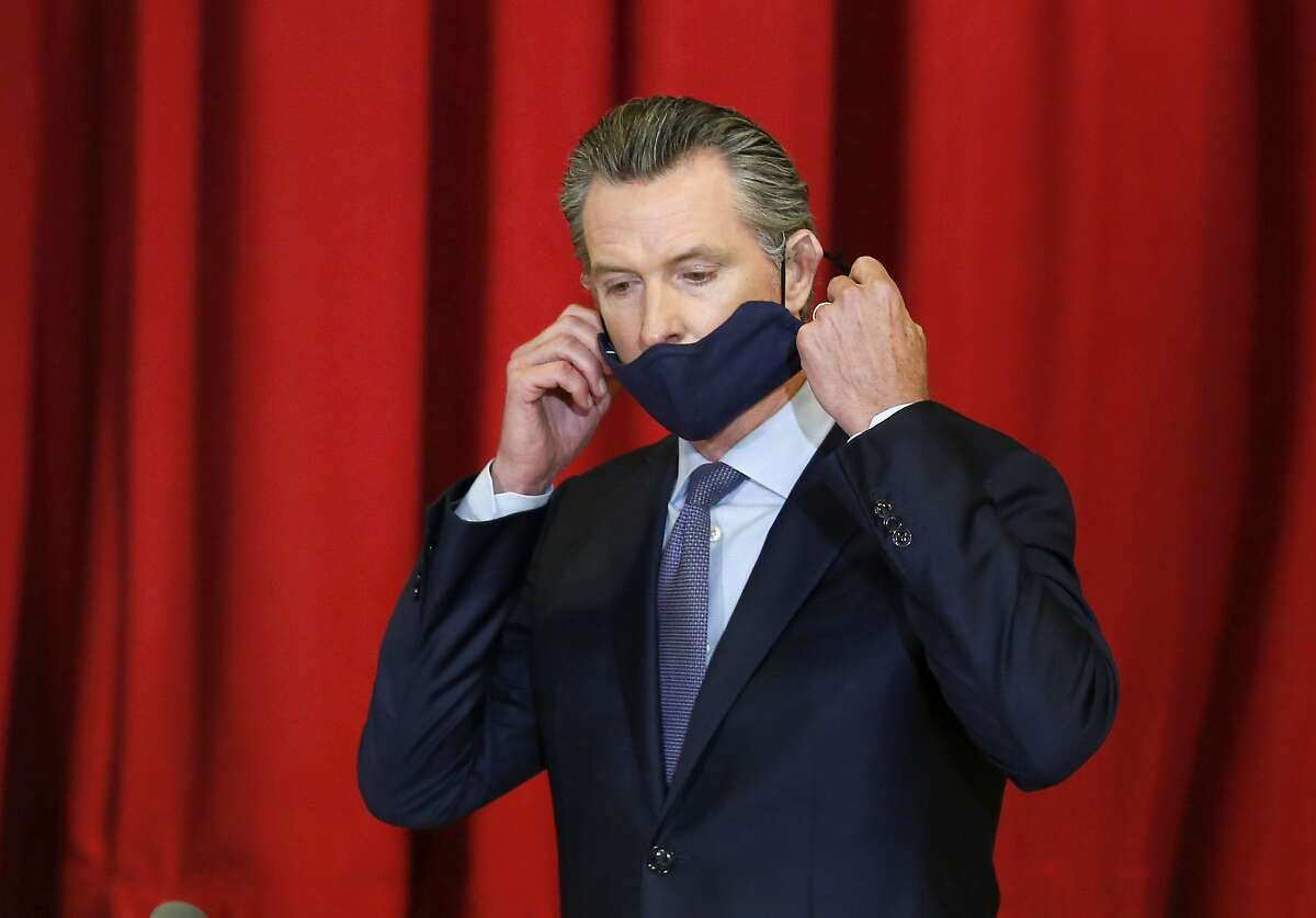 FILE - In this June 1, 2020 file photo, California Gov. Gavin Newsom takes off his face mask before news conference after meeting leaders of the African American community in Sacramento, Calif.