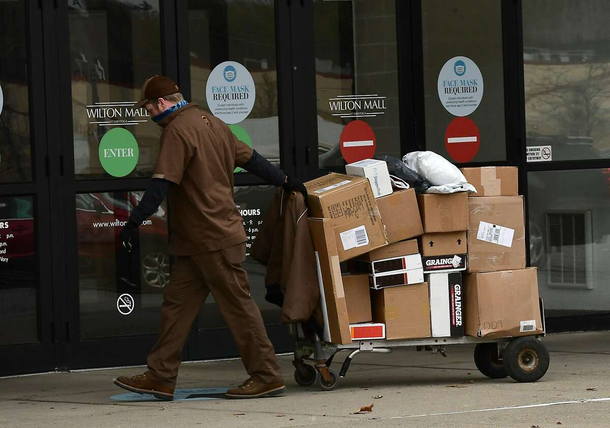 A driver delivers packages in Winton, N.Y. for UPS, which said it planned 100,000 holiday hires.