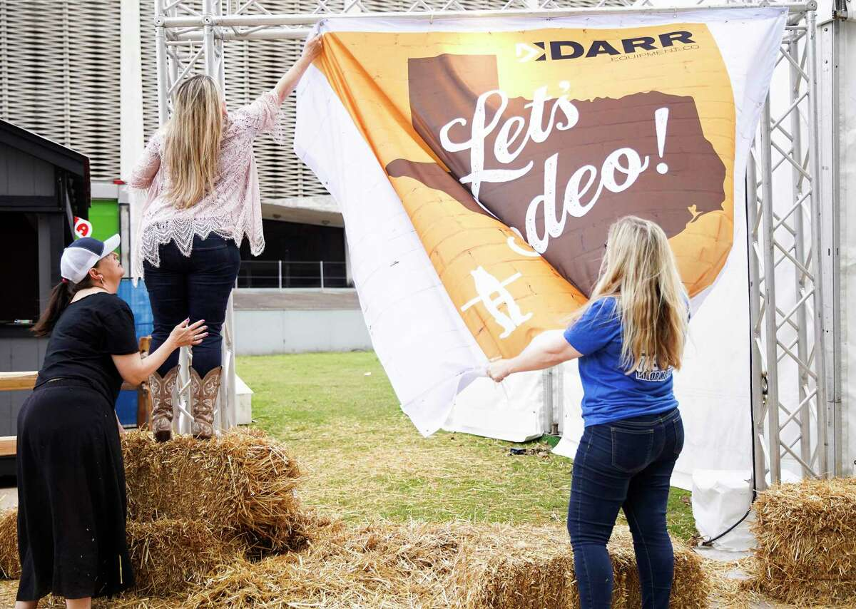 Darry Equipment Co., employees take down their sign after the Houston Livestock Show and Rodeo close early on Wednesday, March 11, 2020.