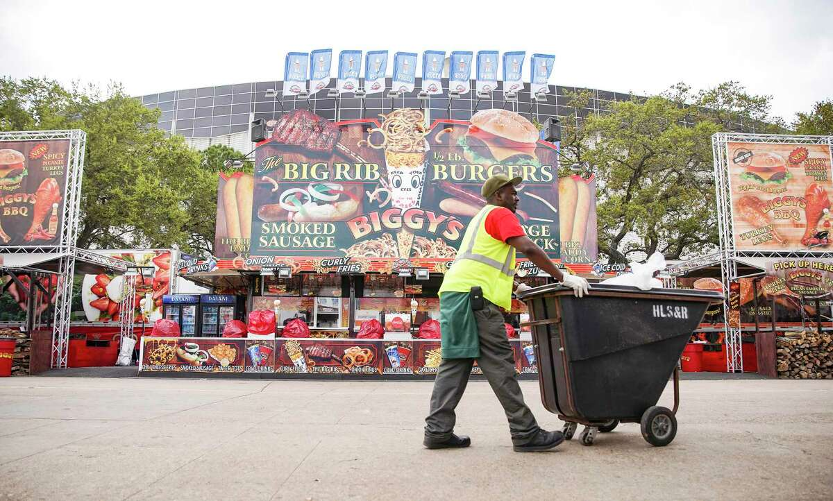 A worker picks up trash after the Houston Livestock Show and Rodeo announcement of the rodeo closing early on Wednesday, March 11, 2020.