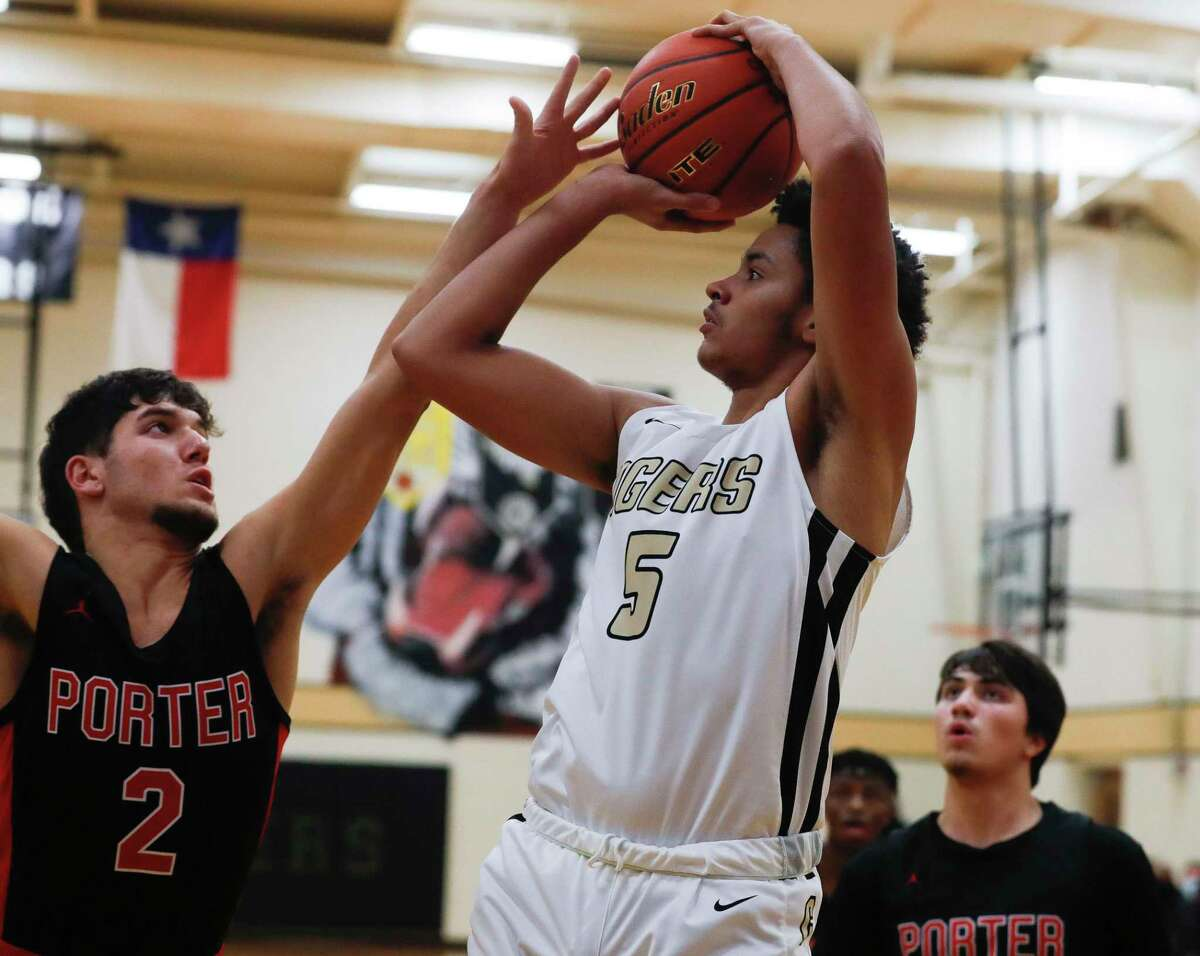 Conroe's Jalen Cardenas (5) shoots as Porter's Abdul Mugsit (5) defends during the first quarter of a non-district high school basketball game at Conroe High School, Tuesday, Dec. 8, 2020, in Conroe.