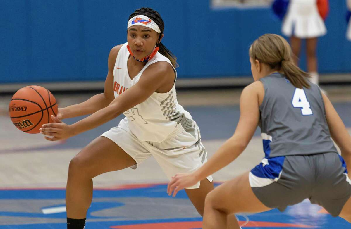 Grand Oaks shooting guard Kaitlyn Stewart (24) drives the ball while under pressure from New Caney point guard Jasmine Toney (4) during the second quarter of a non-district girls basketball game at Grand Oaks High School in Spring.