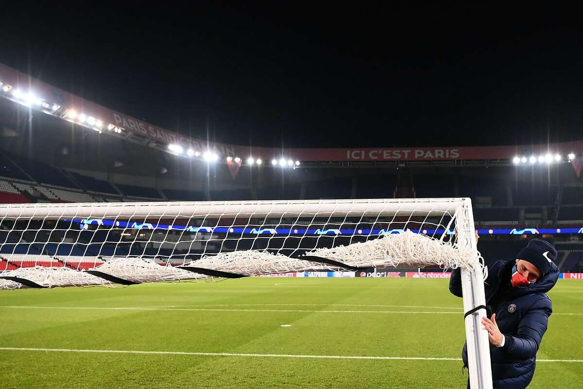 A Parc des Princes stadium employee removes a goal in Paris on December 8, 2020 after suspended UEFA Champions League group H football match between Paris Saint-Germain (PSG) and Istanbul Basaksehir FK was postponed on December 9. - Paris Saint-Germain's decisive Champions League game with Istanbul Basaksehir was suspended today in the first half as the players walked off amid allegations of racism by one of the match officials. The row erupted after Basaksehir assistant coach Pierre Webo, the former Cameroon international, was shown a red card during a fierce row on the touchline with staff from the Turkish club appearing to accuse the Romanian fourth official of using a racist term. (Photo by FRANCK FIFE / AFP) (Photo by FRANCK FIFE/AFP via Getty Images)