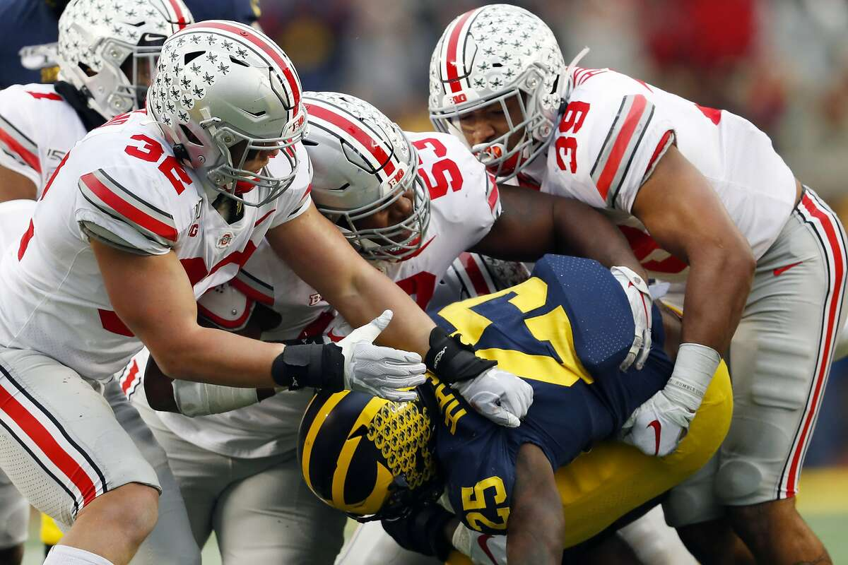 Ohio State's Tuf Borland (32), Davon Hamilton (53) and Malik Harrison (39) smother Hassan Haskins of Michigan during last year's game, a 56-27 OSU victory in Ann Arbor, Mich.