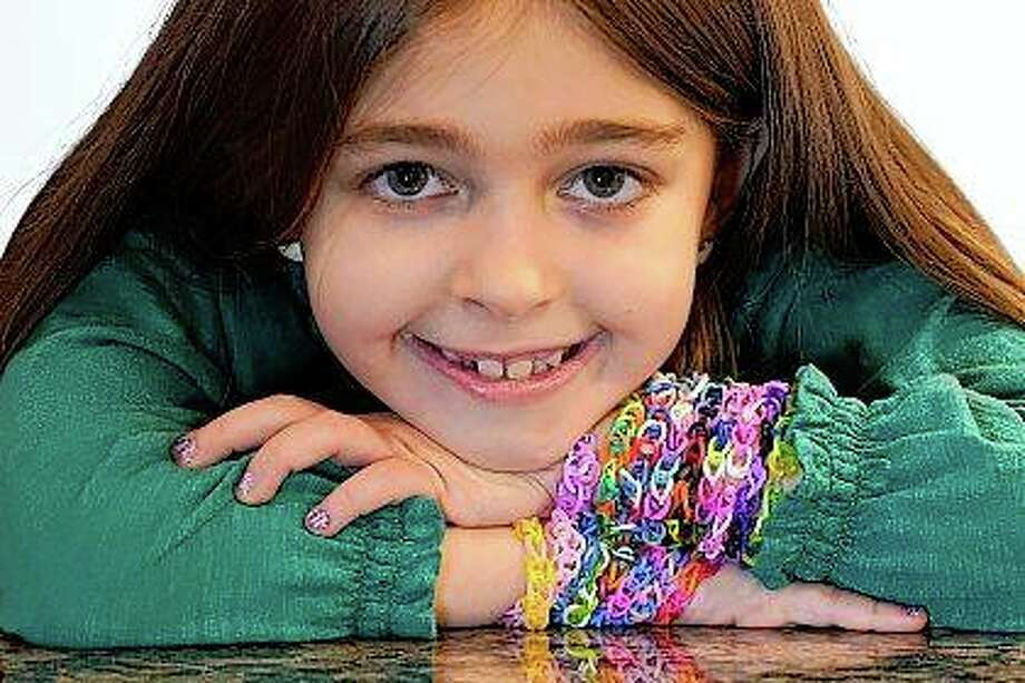Hayley Orlinsky wears several colorful rubber band bracelets she makes in her Chicago home. The 7-year-old has spent most of the coronavirus pandemic crafting the bracelets as a fundraiser, earning nearly $20,000, to buy personal protective equipment for Ann and Robert H. Lurie Children's Hospital. Photo: Charles Rex Arbogast   Associated Press