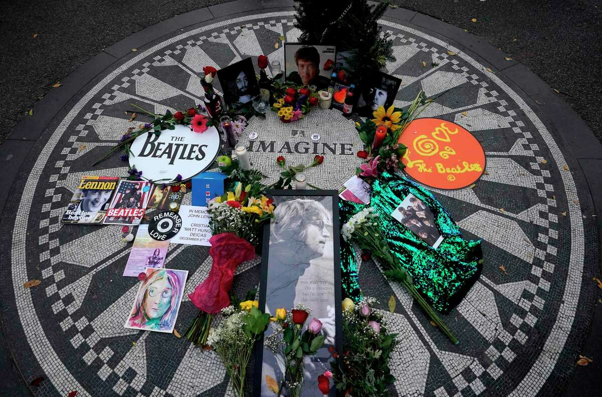 Pictures on a monument as mourners gathered on the 40th anniversary of John Lennon's death, at Strawberry Fields in Central Park to honor the late Beatles star in New York on Dec. 8, 2020.