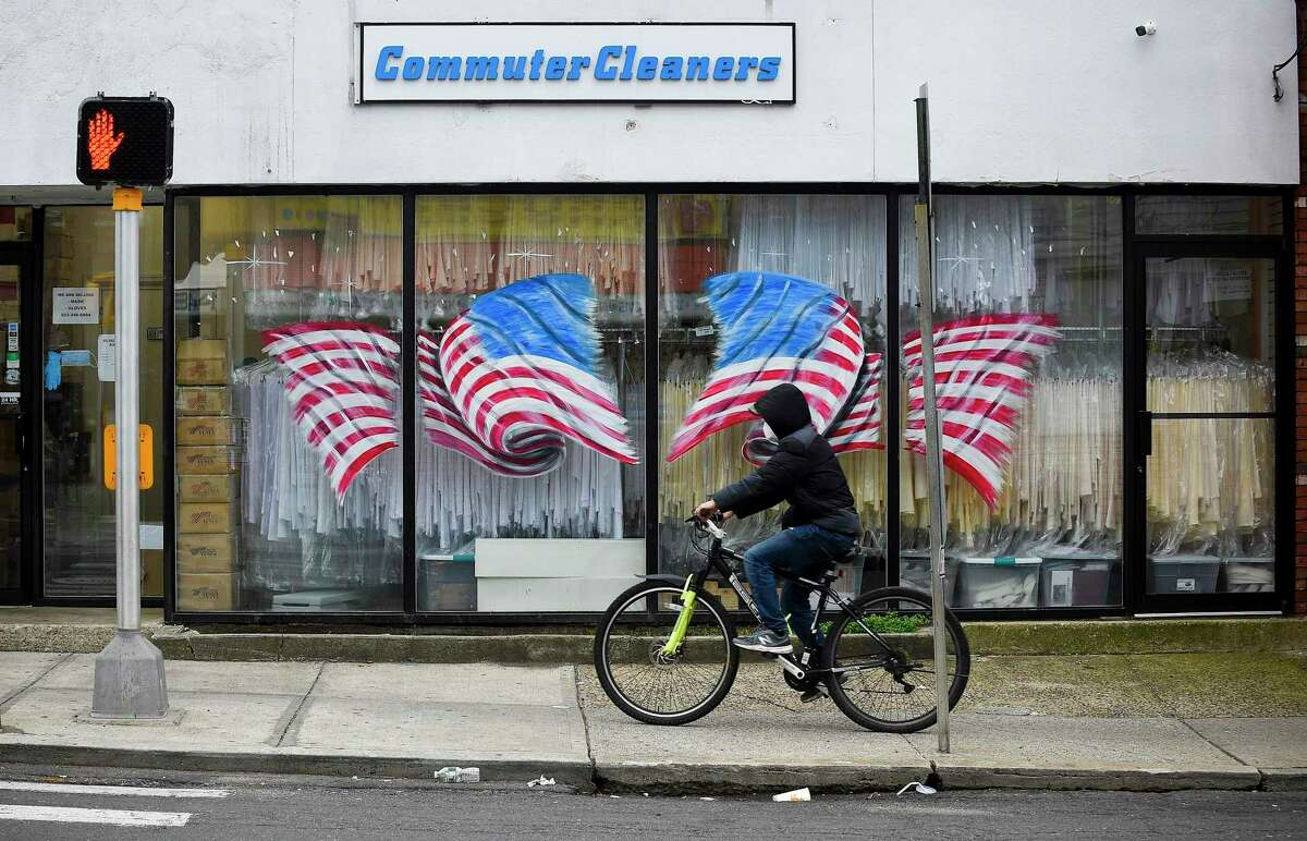 A bicyclist passes in front of American Flags displayed on the windows of Stamford Uniform in Stamford, Connecticut on April 29, 2020. Owner Paul McDonald has seen a dramatic decrease in business as a direct result of the COVID-19 pandemic.