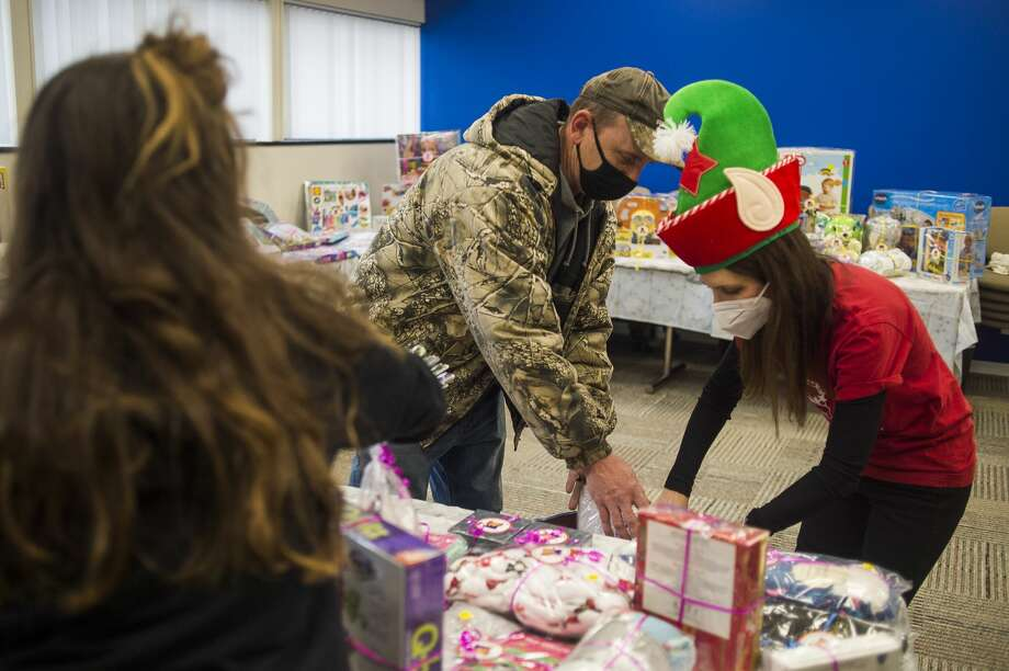 Mickey Guisewite of The Bottomless Toy Chest, right, helps Charles Colley of Midland, left, place toys for his daughters into a bag during a toy giveaway for families impacted by the dam failures and flood in May hosted by United Way of Midland County and The Bottomless Toy Chest Tuesday, Dec. 8, 2020 in Midland. (Katy Kildee/kkildee@mdn.net) Photo: (Katy Kildee/kkildee@mdn.net)