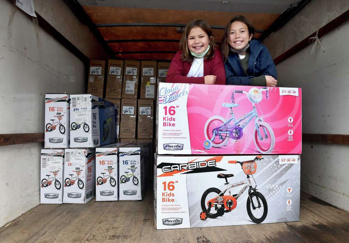 Abigail DellaVentura, left, 10, and her sister, Grace, 12, stand with some of the bicycles purchased with money they raised in the Wishing Wheels Bike Drive in Guilford on December 5, 2020.