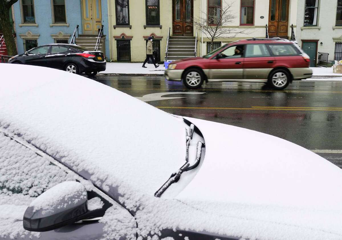 Snow covers the windshield of a car parked on Madison Ave. on Wednesday, Dec. 9, 2020, in Albany, N.Y. (Paul Buckowski/Times Union)