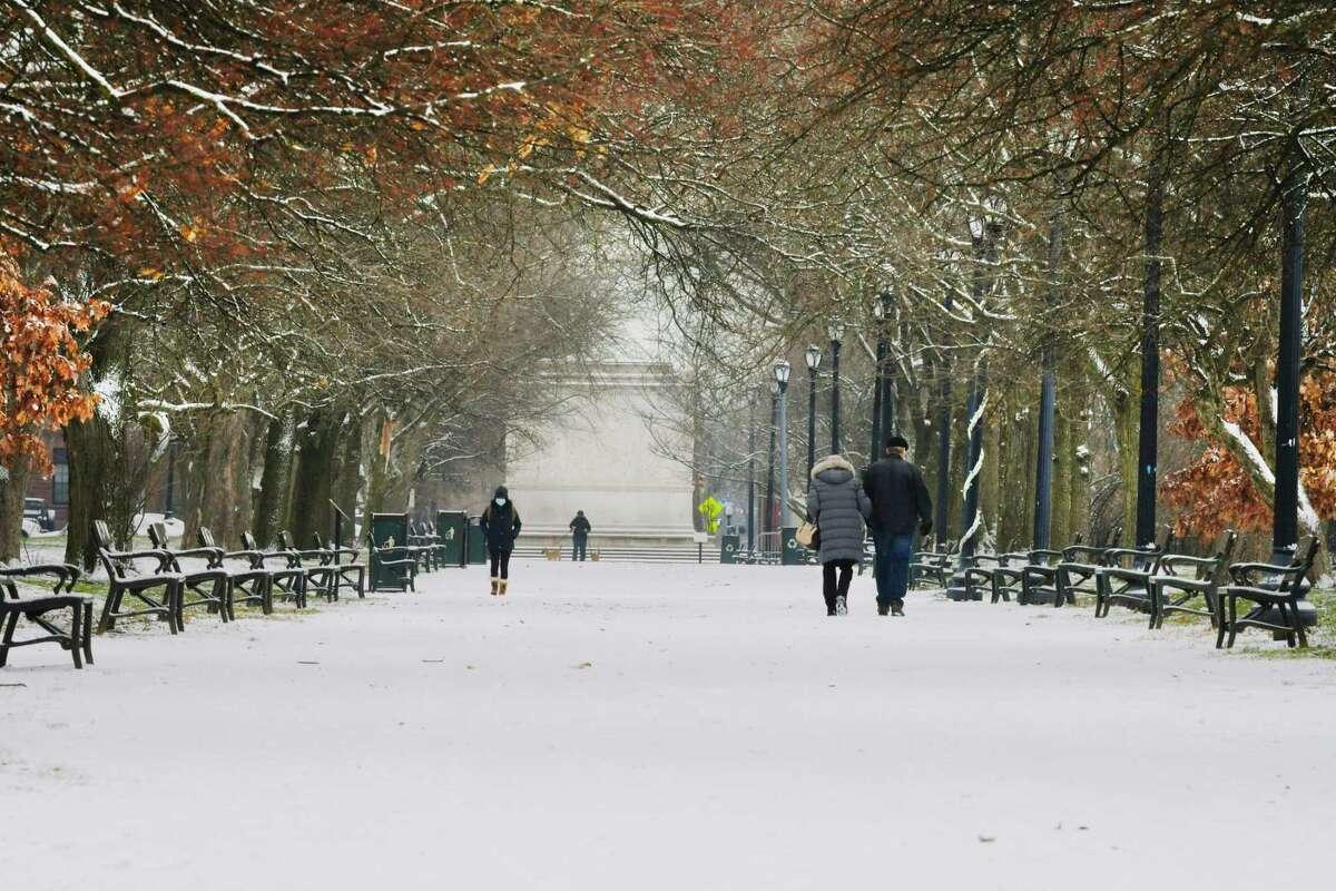 People walk on the freshly fallen snow in Washington Park on Wednesday, Dec. 9, 2020, in Albany, N.Y. (Paul Buckowski/Times Union)