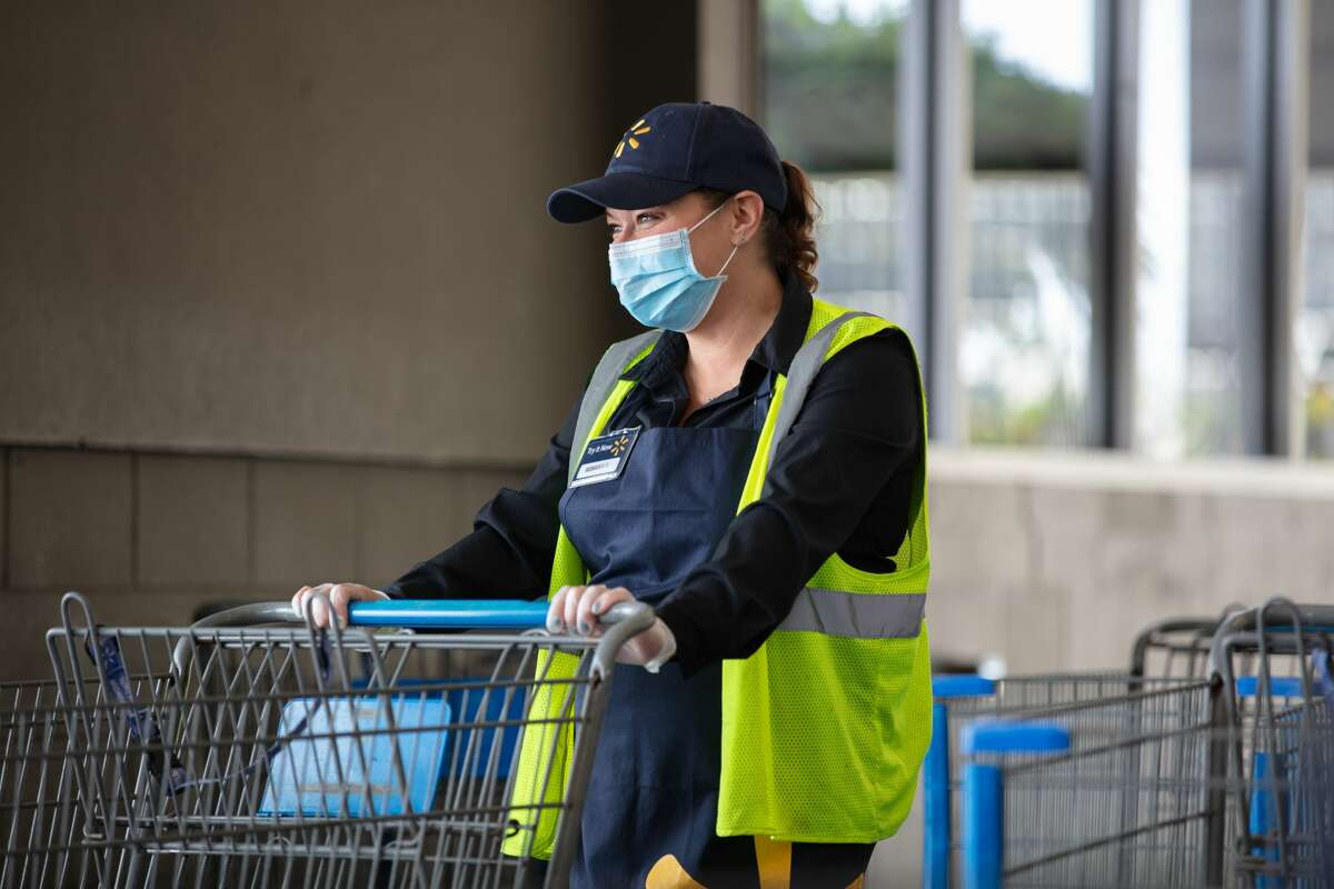 A Walmart associate wears a mask while moving carts.