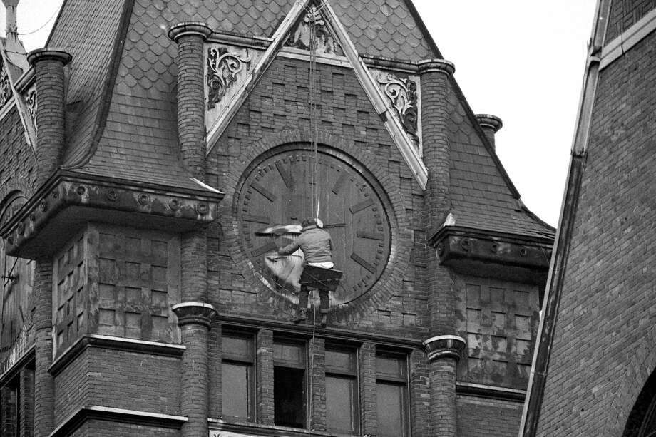 "From the front page of the News Advocate on Dec. 10, 1980, ""Al Blue, the steeplejack, repairs the clock on the steeple of First Congregational Church.""(Manistee County Historical Museum photo)"