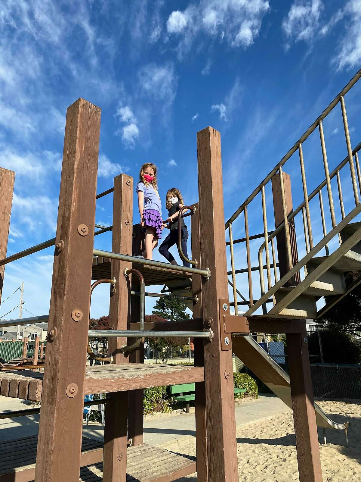 Lara Helland, 7, left, stands on a play structure with her friend at Miraloma Playground on Dec. 6, 2020, just hours before it closes due to a new coronavirus stay-at-home order.