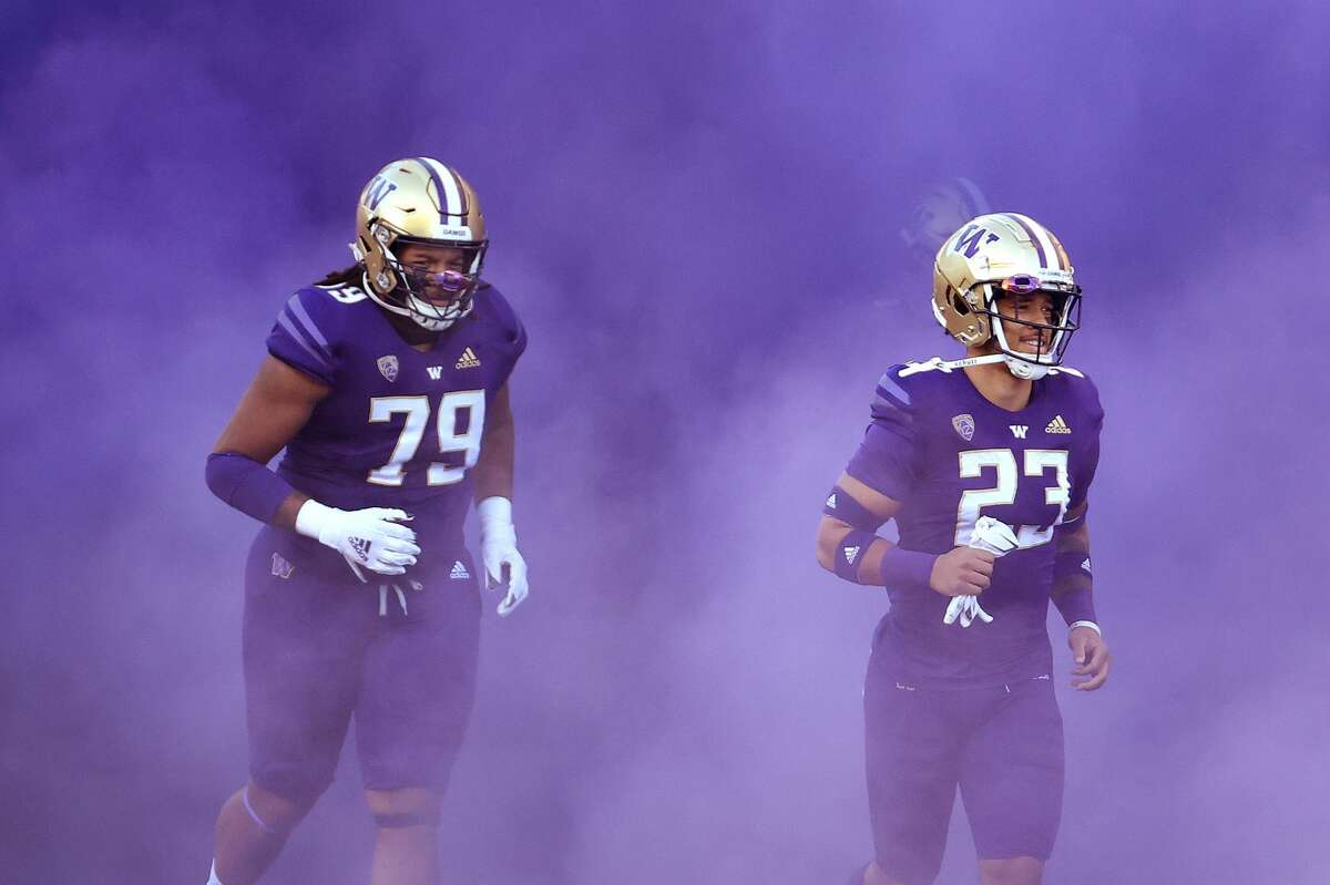 SEATTLE, WASHINGTON - DECEMBER 05: Victor Curne #79 and Brandon McKinney #23 of the Washington Huskies take the field before their game against the Stanford Cardinal at Husky Stadium on December 05, 2020 in Seattle, Washington. (Photo by Abbie Parr/Getty Images)