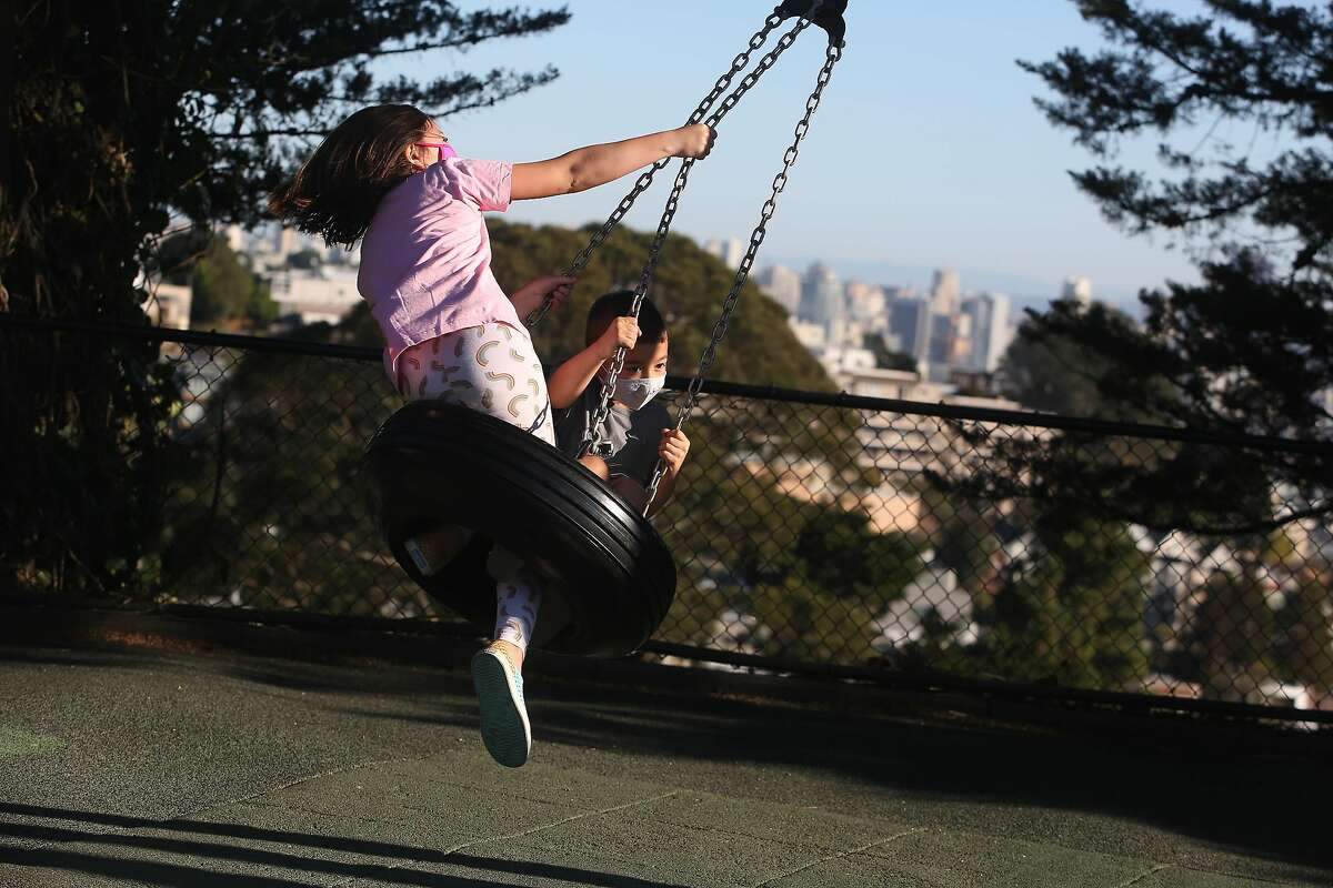 Kira Knox (l to r), 10, and her brother Nathan Knox, 6, play on a tire swing at Walter Haas Playground on Wednesday, October 14, 2020 in San Francisco, Calif. Playgrounds in San Francisco have reopened with restrictions since being closed in March.