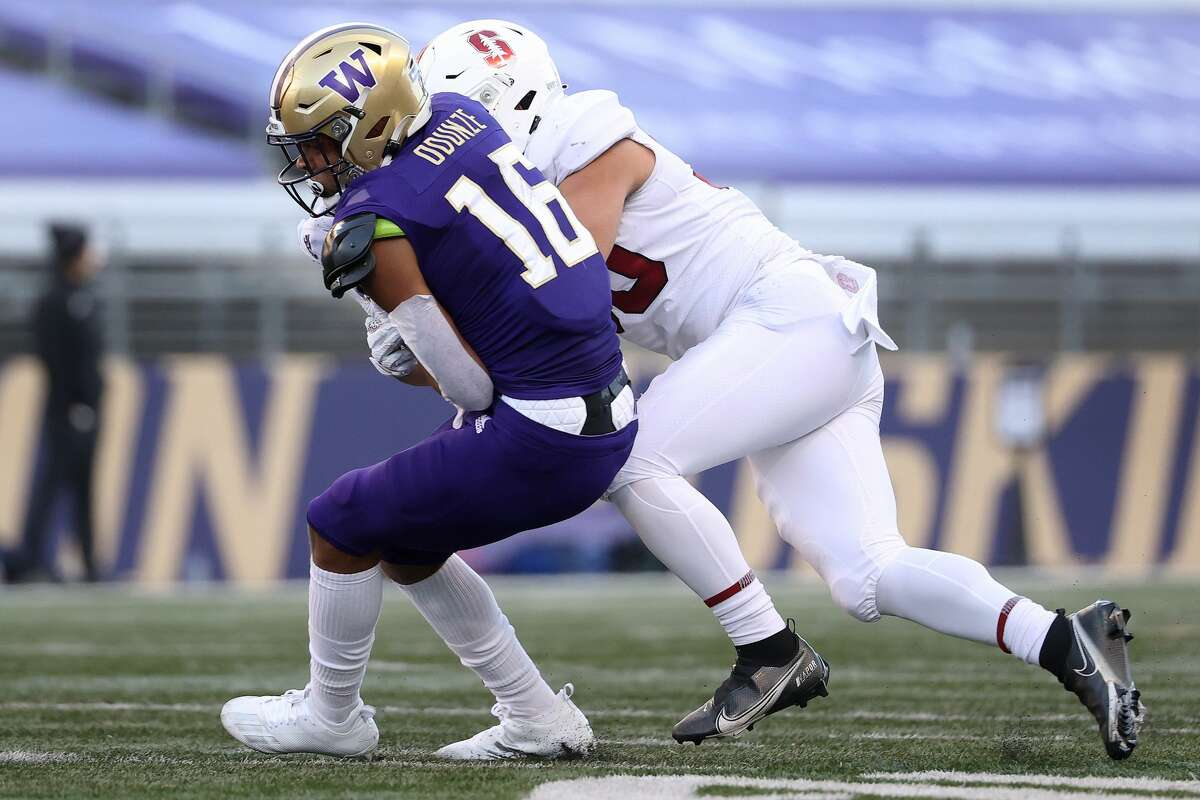 SEATTLE, WASHINGTON - DECEMBER 05: Rome Odunze #16 of the Washington Huskies is tackled by Gabe Reid #90 of the Stanford Cardinal in the third quarter at Husky Stadium on December 05, 2020 in Seattle, Washington. (Photo by Abbie Parr/Getty Images)