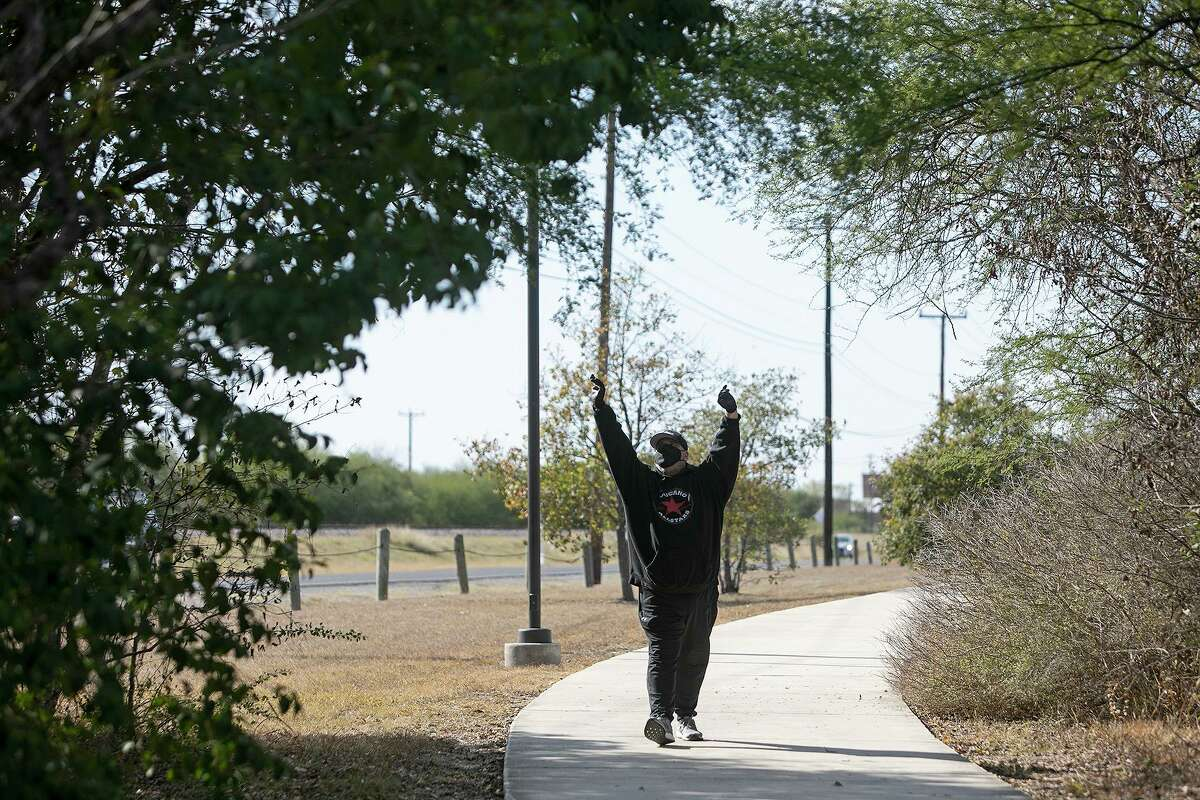 Max Baca stretches as he walks in Kardon Park near his home. He is working to regain his strength so he can sing again.