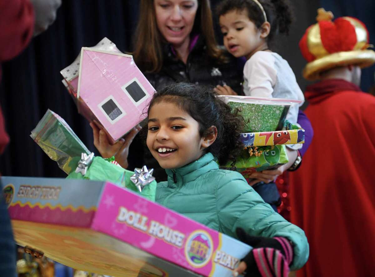Dalia Colon, 7, of Stratford, is excited to receive her gift during the annual Three Kings Day celebration at St. James Church in Stratford, Conn. on Sunday, January 5, 2020.