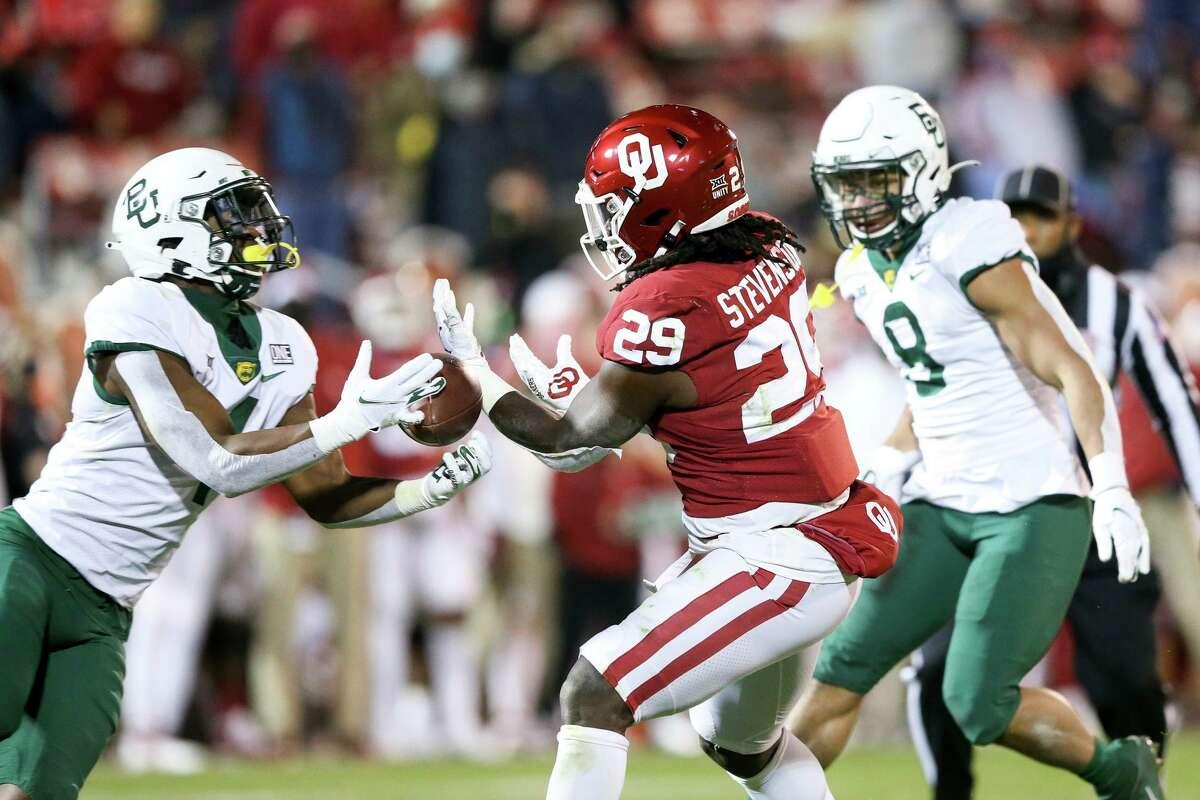 Baylor safety Christian Morgan (4) intercepts a pass intended for Oklahoma running back Rhamondre Stevenson (29) during an NCAA college football game in Norman, Okla., Saturday, Dec. 5, 2020. (Ian Maule/Tulsa World via AP)