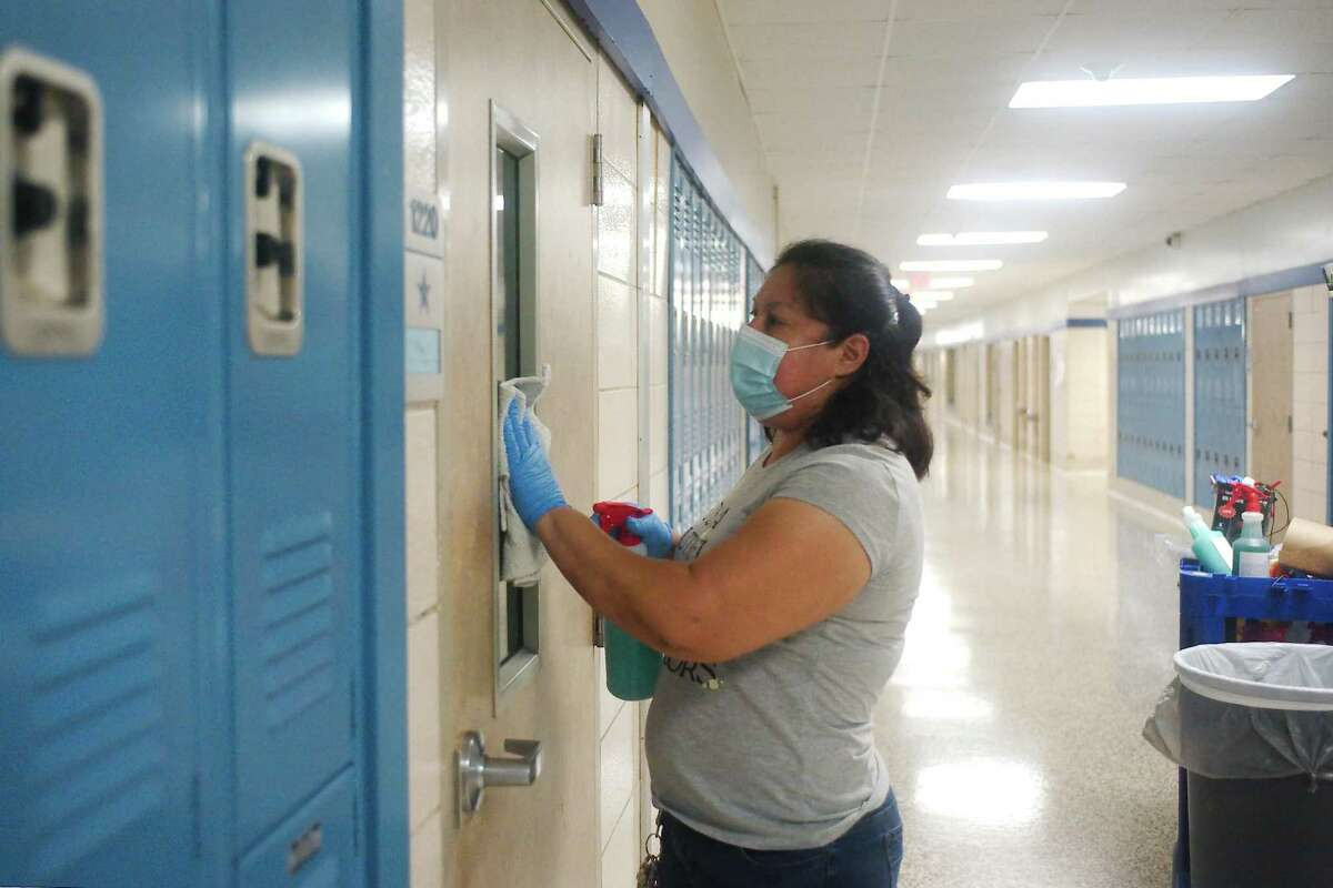 Pasadena ISD employee Rosa Castillo, pictured in July, disinfects the handles and windows of every door at Sam Rayburn High School. Pasadena students failing at least one class in the first semester will no longer have access to online-only classes starting in January, with some exceptions, district officials said.