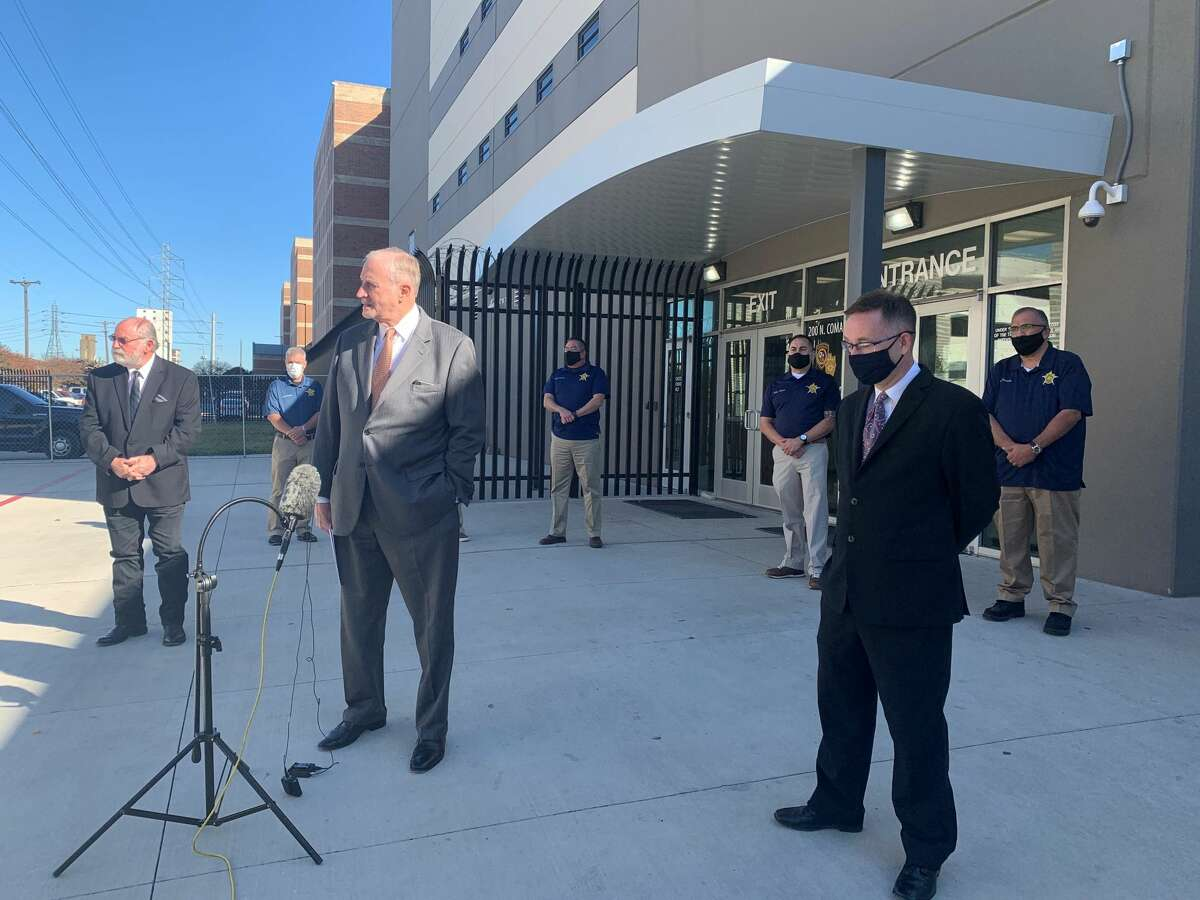 Members of the Deputy Sheriff Association of Bexar County and Combined Law Enforcement Associations of Texas discuss low morale among Bexar County jail detenion deputies outside the jail Wednesday.