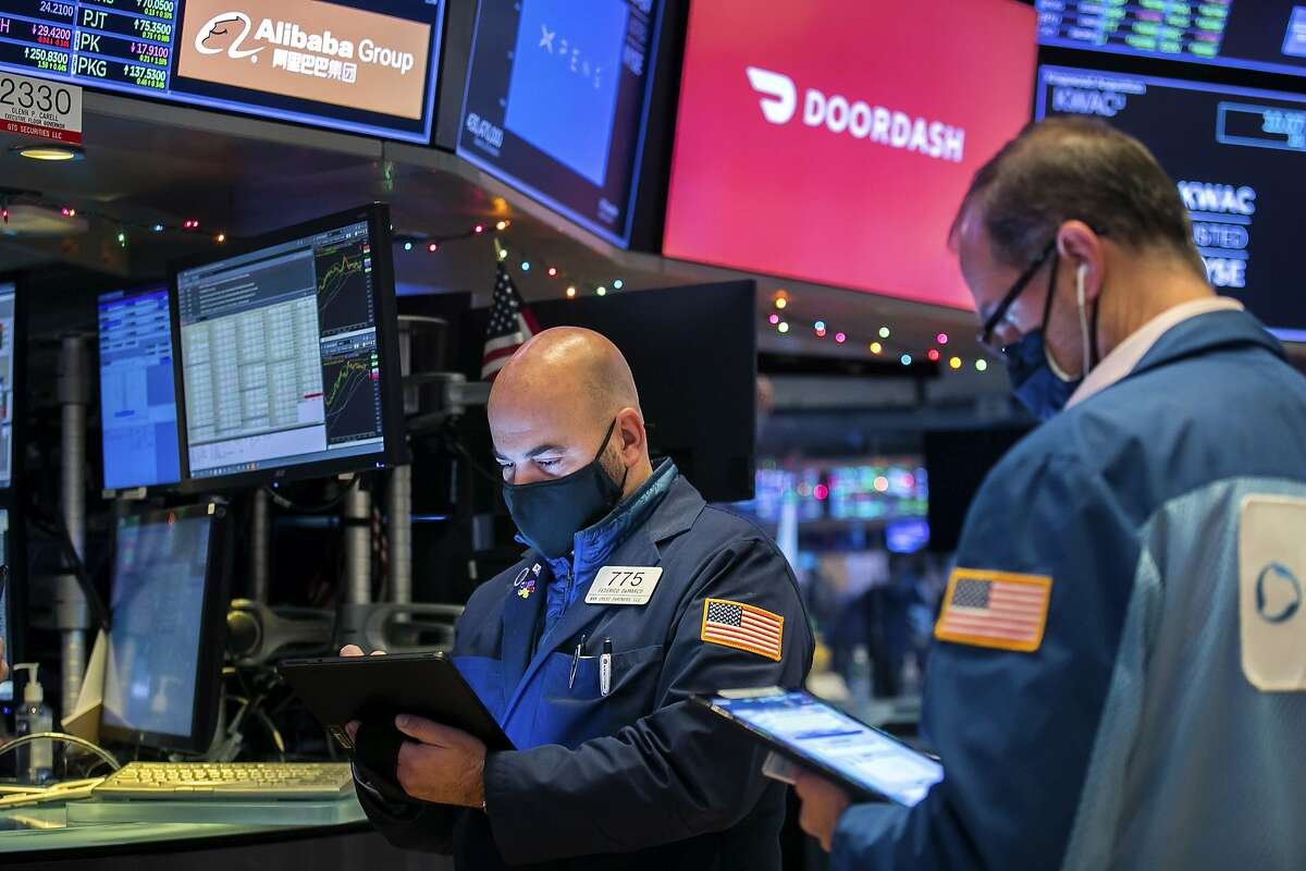 Traders on the New York Stock Exchange watch DoorDash's worth climb to $72 billion on its first day of trading as a public company Wednesday.