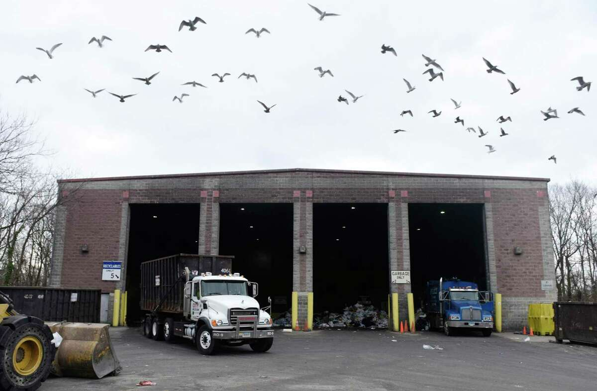 A flock of seagulls flies away as trucks dump trash in the commercial dumping bay at the Holly Hill Transfer Station in Greenwich, Conn. Monday, Jan. 27, 2020.