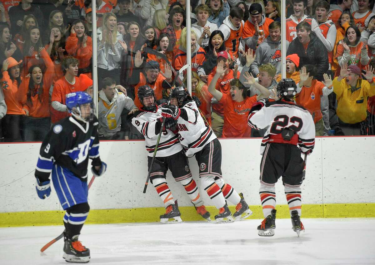 Kalieigh's Krew (dressed in orange) help New Canaan's Jack Johnson (9) celebrate a second period goal against Darien in an FCIAC boys hockey game at the Darien Ice House on Feb. 8, 2020 in Darien, Connecticut. As show of unison, both teams wore orange laces to honor New Canaan student Kaleigh Griffiths, who lost her battle with leukemia. The New Canaan Rams dedicated the game in honor of Kaleigh.