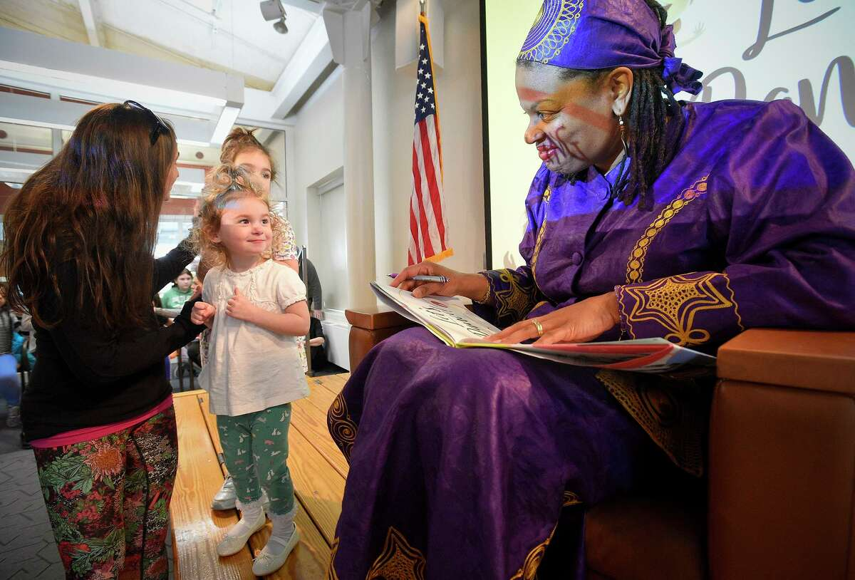 Cordelia Fallon, 2, of Fairfield and her older sister Inara have a copy of the newly released children's book 'Let's Dance,