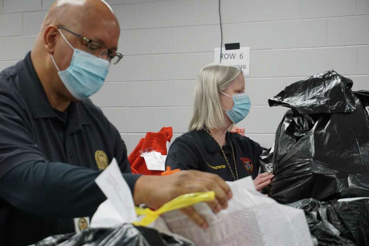 Ivan Nelson, left, and Liz Loocke of the Katy Independent School District Police Department sort through gifts wrapped and prepared for the Santa Cops program on Tuesday, Dec. 8. This year, Santa Cops will give Christmas presents to around 1,200 children.