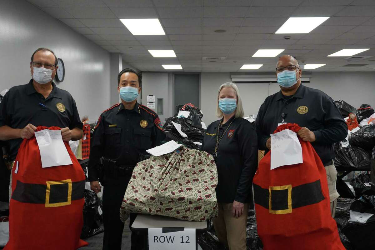 Keith Meier, from left, Henry Gaw, Liz Loocke and Ivan Nelson of the Katy Independent School District Police Department, pose on Tuesday, Dec. 8, with Christmas gifts prepared for Santa Cops, a program that is set to distribute wrapped clothes and toys to around 1,200 children.