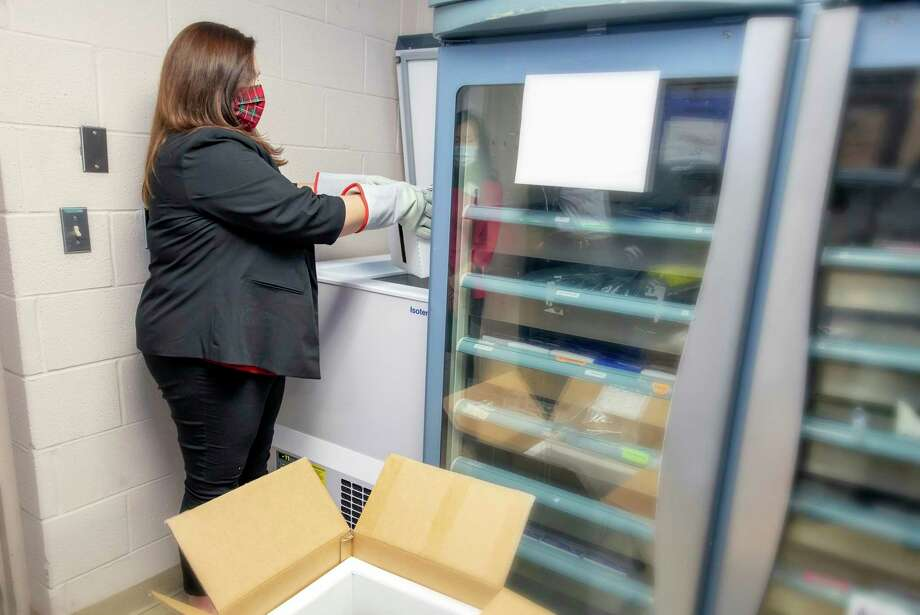 """In preparation of the receipt of the COVID-19 vaccine, pharmacy buyer Stephanie Jenkins processes a Pfizer """"test box"""" that was recently received at the MidMichigan Medical Center-Midland on Dec. 9, 2020. (Photo provided/Millie Jezior)"""