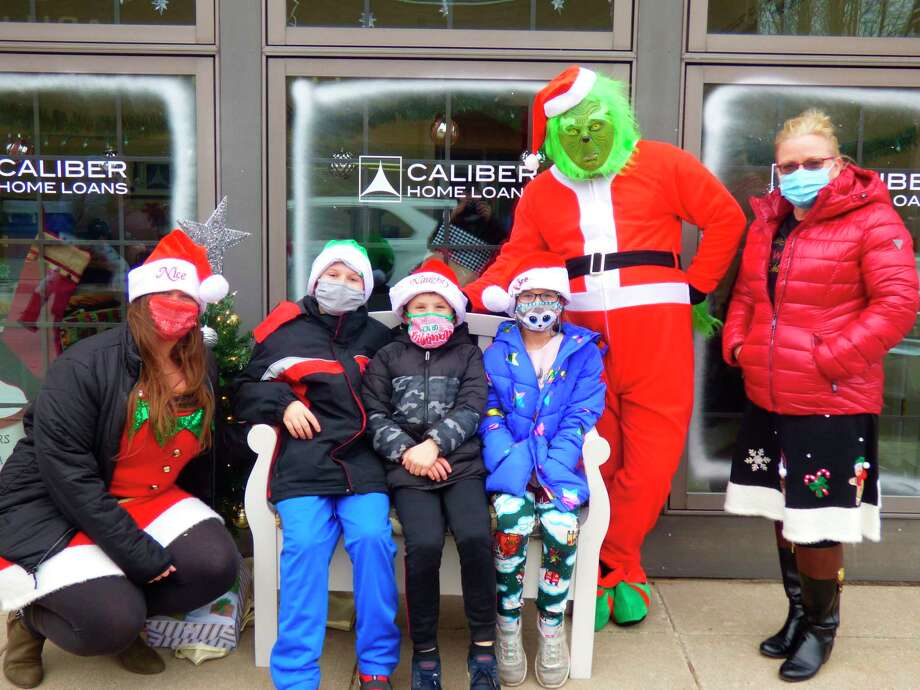 The Grinchposes for a photograph in front of Caliber Home Loanswith members of theSedelmaier family (from left) Amber, Jason, Remy, Hazel, Justin (as the Grinch) and Mindy. (Scott Fraley/News Advocate)