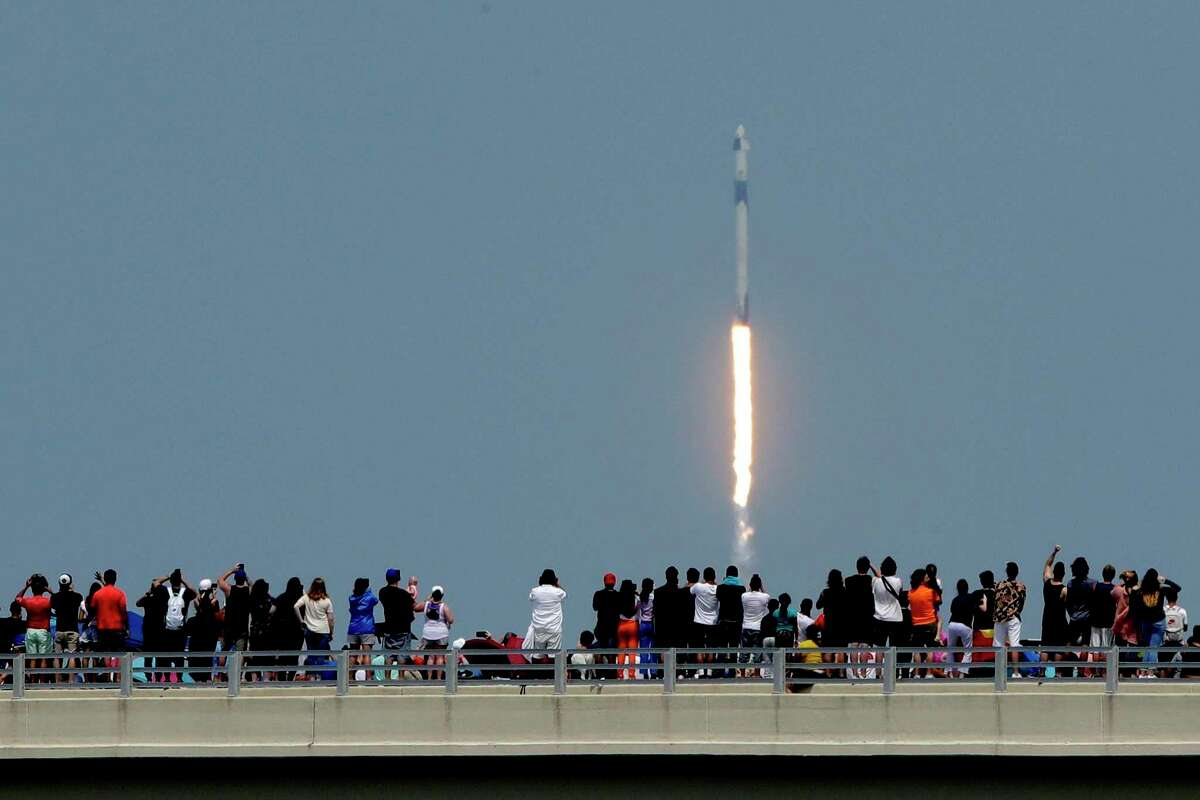 Spectators watch from a bridge in Titusville, Fla., as SpaceX Falcon 9 lifts off with NASA astronauts Doug Hurley and Bob Behnken in the Dragon crew capsule, Saturday, May 30, 2020, from the Kennedy Space Center at Cape Canaveral, Fla. The two astronauts are on the SpaceX test flight to the International Space Station. For the first time in nearly a decade, astronauts blasted toward orbit aboard an American rocket from American soil, a first for a private company. (AP Photo/Charlie Riedel)